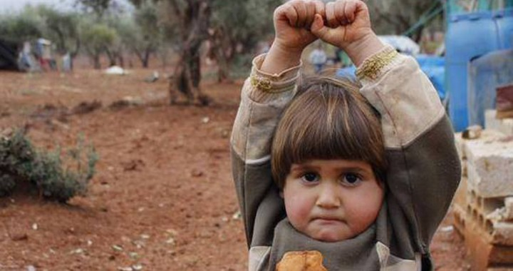 four-year-old Hudea lifts her hands in surrender. Taken by Osman Sağırlı at the Atmeh refugee camp in Syria 2012